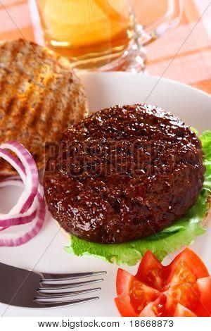 hamburguesa de carne abierta clásica con cerveza en el fondo, DOF superficial