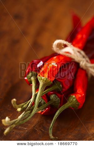 red hot chillies pepper bunch in  wooden bowl  background, shallow dof