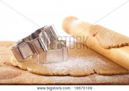 christmas gingerbread  cookie cutters on dough with rolling pin,white backdrop