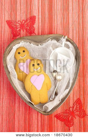 gingerbread boy and girl on tin heart shaped tray, red linen striped with butterfly backdrop