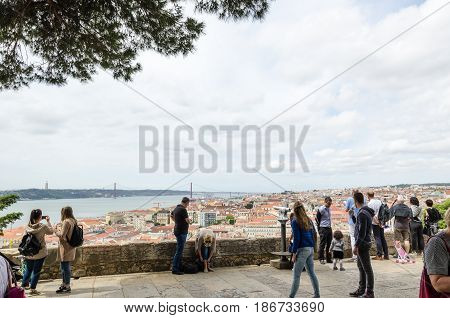 LISBON, PORTUGAL - APRIL 26: Tourists looking at the view from the old castle Sao Jorge in LisbonPortugal on April 26, 2017