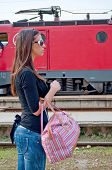 picture of loco  - Girl with bag waiting for train with loco in the background - JPG