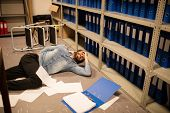 Documents scattered by fallen businessman in file storage room at workplace poster