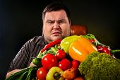 Diet fat man eating healthy food with vegetables cauliflower and sweet pepper with radish, tomatoes  poster