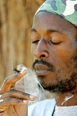 image of rastafari  - Rastafarian man smoking cannabis - JPG