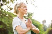 Mature woman in park joining hands with closed eyes and meditates. Relaxed senior woman with joined  poster
