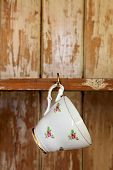 image of shabby chic  - tea cup hanging on a hook in old wooden cupboard - JPG