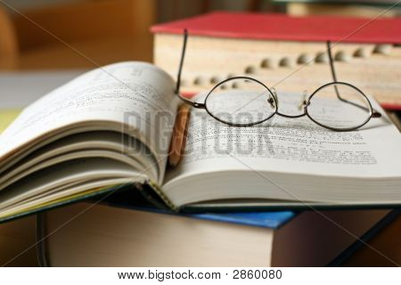 Text Books On Table With Glasses And Pencil