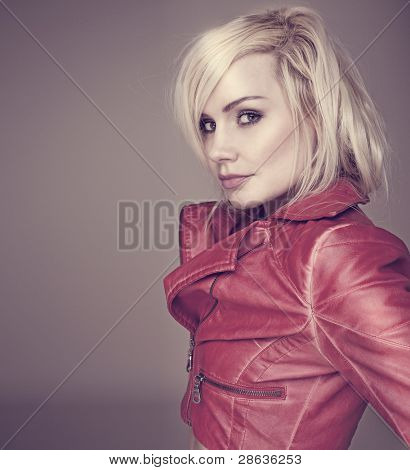 Fashion studio shot of attractive young blonde woman in stylish leather jacket