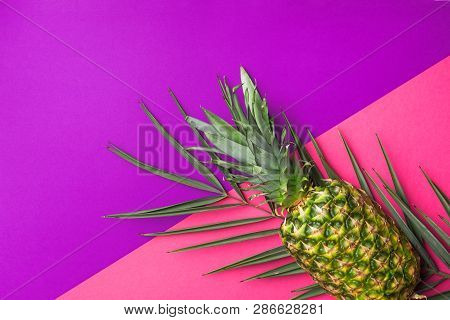 poster of Ripe Pineapple On Green Palm Leaf On Duotone Fuchsia Pink Vibrant Violet Background. Trendy Funky St