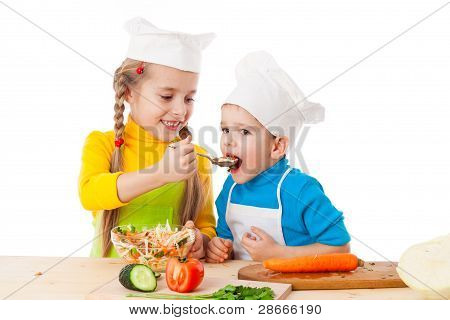 Two kids eating salad