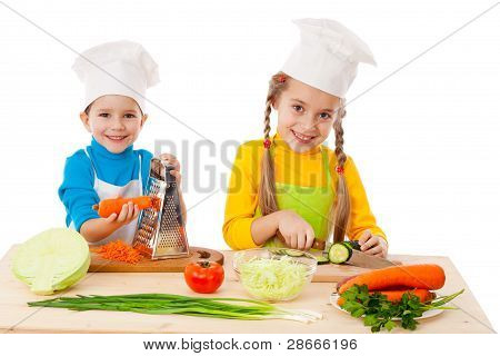 Two kids making salad