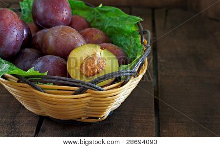 Basket Of Fresh Plums On Old Wooden Table