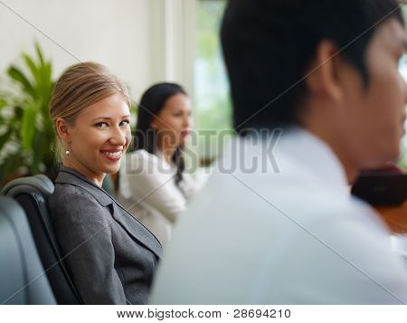 Businesspeople Talking In Meeting Room And Woman Smiling