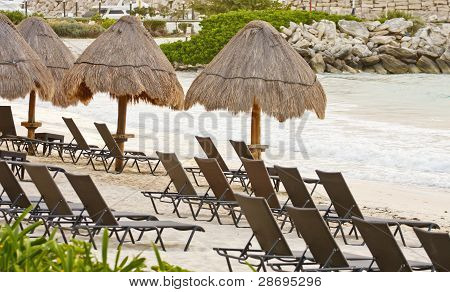 Chairs On Beach Near Straw Umbrellas