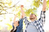 Excited Couple Celebrating Success Raising Arms In A Park With Trees In The Background poster