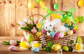 Easter composition with little white bunny in basket,  spring flowers and colorful Easter eggs . Eas poster