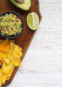 Guacamole With Corn Nachos, Lime, Cut Half Avocado On Wooden Board. White Wooden Surface. Top View.  poster