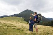 Father And Son With Backpacks Hiking Together In Summer Mountains. Back View Of Dad And Child Holdin poster