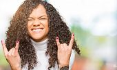 Young beautiful woman with curly hair wearing turtleneck sweater shouting with crazy expression doin poster