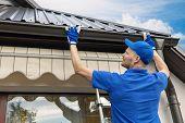 Man Installing House Roof Rain Gutter System poster