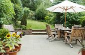 London Garden In Summer With Patio, Wooden Garden Furniture And A Parasol Or Sun Umbrella poster