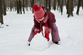 stock photo of ruddy-faced  - The little girl was lying a snowman in winter - JPG
