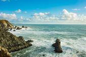 Waves crashing over the rocks on the California coast near San Francisco. poster