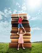 Little Girl And Boy Climbing On The Tower Made Of Big Books. Childhood Dreams, Reading And Education poster