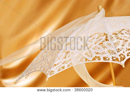 Beautiful lace parasol with chiffon ribbon on gold satin background with copy space.  Close-up with shallow dof.  Ideal for use as a bridal shower invitation.