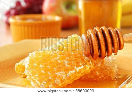 Sunlit still life of golden honeycombs with fresh honey and drizzler.  Jars of honey and fresh fruit in background.  Closeup with shallow dof.