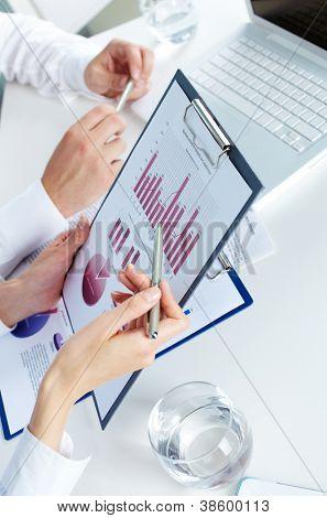 Imagen de manos humanas durante la discusión de documentos de negocios en reunión