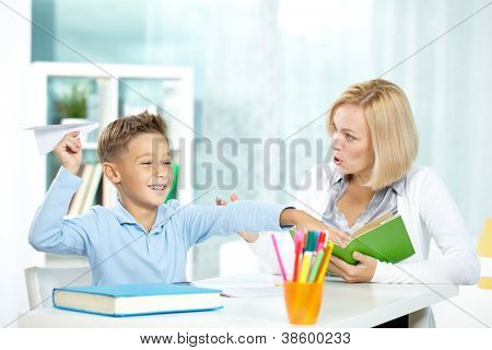Portrait of naughty boy playing with paper plane at workplace and his indignant tutor looking at him