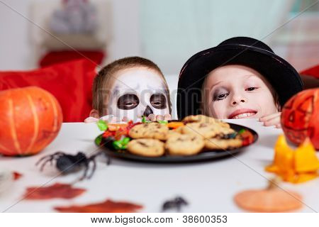 Photo of two eerie boys looking at cookies on Halloween table