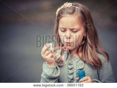 Portrait of funny lovely little girl blowing soap bubble