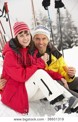 Middle Aged Couple Eating Sandwich On Ski Holiday In Mountains