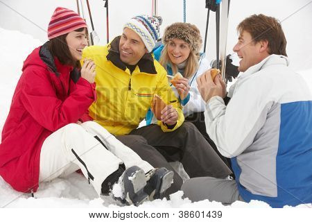 Group Of Middle Aged Friends Eating Sandwich On Ski Holiday In Mountains