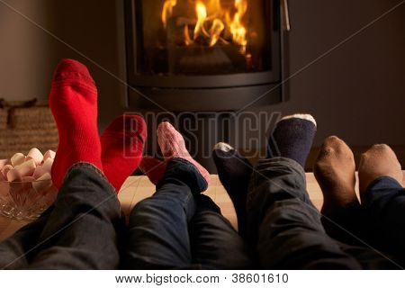 Close Up Of Familys Feet Relaxing By Cosy Log Fire With Marshmallows