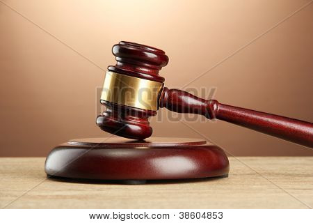 wooden gavel on wooden table, on brown background