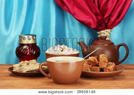 Teapot with cup and saucers with oriental sweets - sherbet, halva and turkish delight on wooden table on a background of curtain close-up
