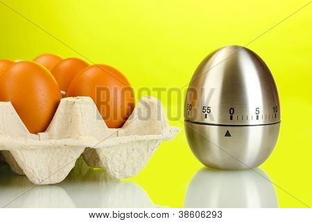 eggs in box and egg timer on green background