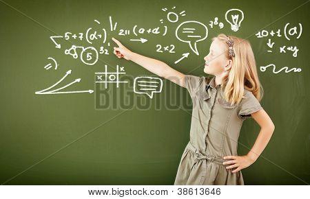 Scoolgirl stehend in Klasse in der Nähe von einer grünen Tafel