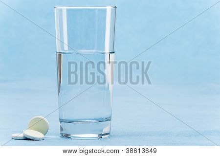 Soluble tablet throw in water glass on blue background