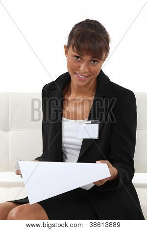 Businesswoman wearing an ID badge and reading a document