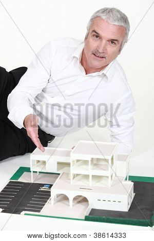 Senior architect laying by model building