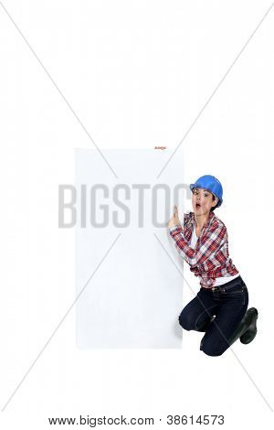 A female construction worker pointing at a poster.