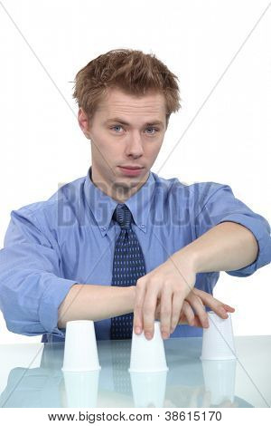 A businessman doing a cup trick.