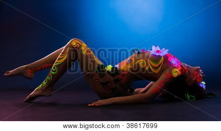 Sexy woman lay in glowing flowers and uv make-up