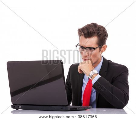Closeup portrait of a young business man looking serious and working at his laptop isolated on white background