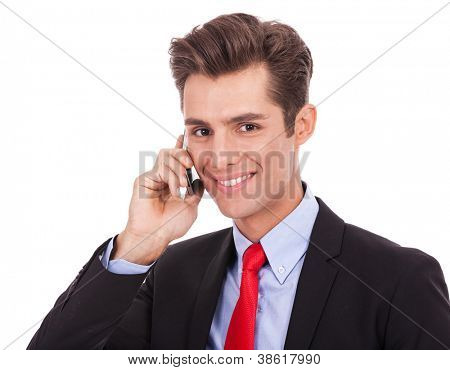 Young smiling business man talking on his smartphone isolated on white background